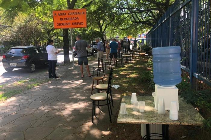 Condomínio disponibiliza cadeiras e água para idosos que aguardam a vacina da gripe em Porto Alegre